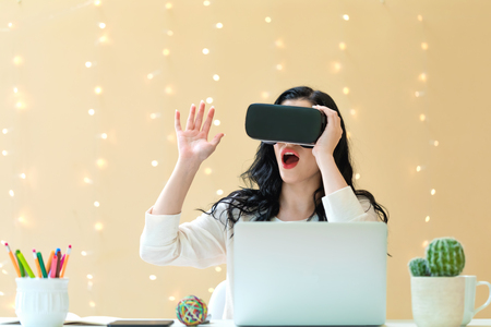 Young woman using a virtual reality headset at a desk against an illuminated wall Stock Photo