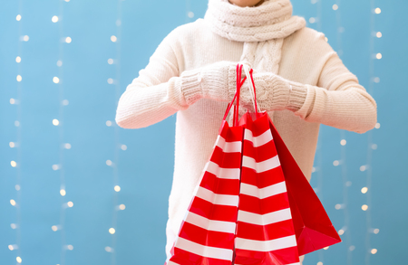 Woman holding shopping bags on a shiny light blue background Stock Photo