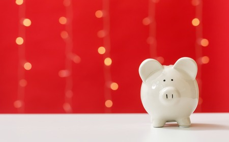 A piggy bank saving and investment theme on a shiny light red background 스톡 콘텐츠