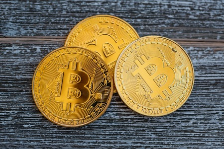 Gold bitcoin cryptocurrency coins on a wooden desk