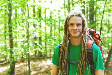 Happy male hiker with backpack trekking through the forest Stock fotó - 113093311