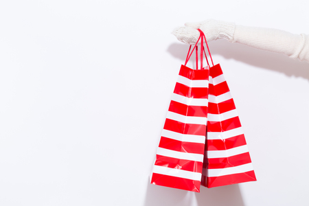 Woman holding shopping bags on a white background