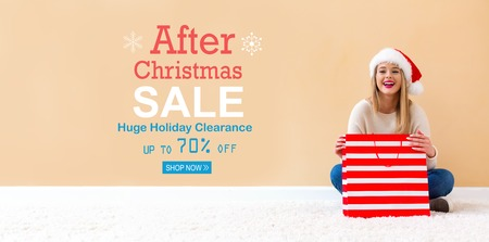 After Christmas sale message with happy woman with Santa hat holding a shopping bag
