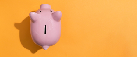 A piggy bank saving and investment theme on a orange background Foto de archivo