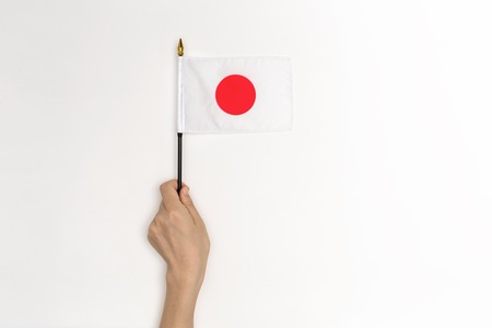 Person holding a Japanese flag on a white background