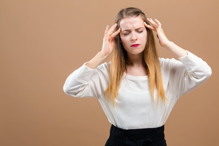 Young woman feeling stressed on a brown background