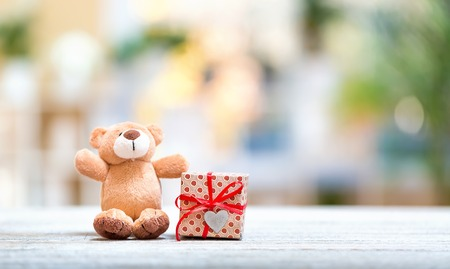 Christmas presents and teddy bear on a bright interior room background 写真素材