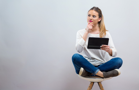 Young woman with a tablet computer on a gray background