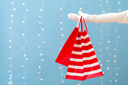 Woman holding shopping bags on a shiny light blue background Stok Fotoğraf