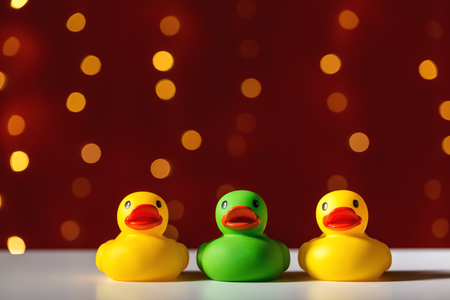 Rubber duck toys on a shiny light dark red background