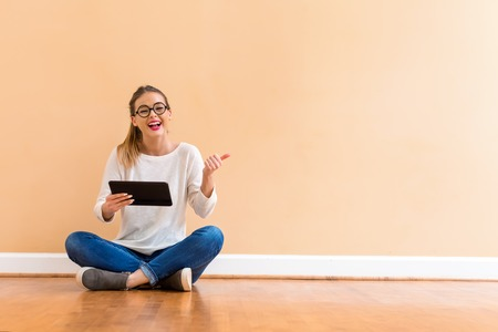 Young woman with a tablet computer against a big interior wall