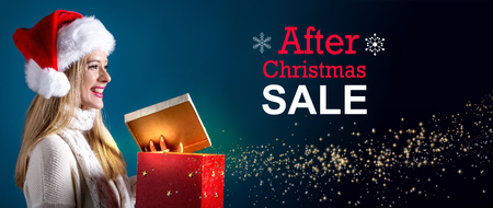 After Christmas sale message with young woman with Santa hat opening a gift box