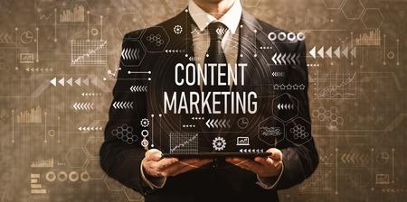 Content-Marketing mit Geschäftsmann, der einen Tablet-Computer auf dunklem Vintage-Hintergrund hält
