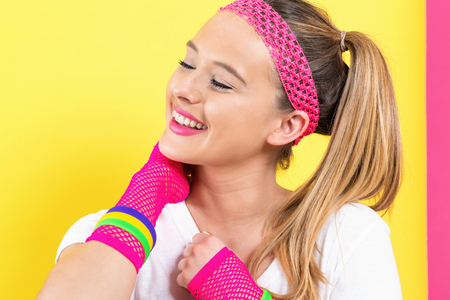 Woman in 1980s fashion theme on a split yellow and pink background Stockfoto - 113170788