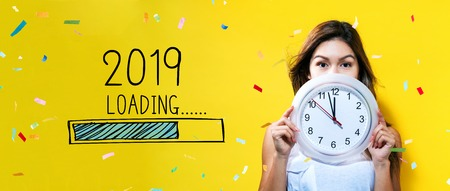 Loading new year 2019 with young woman holding a clock showing nearly 12