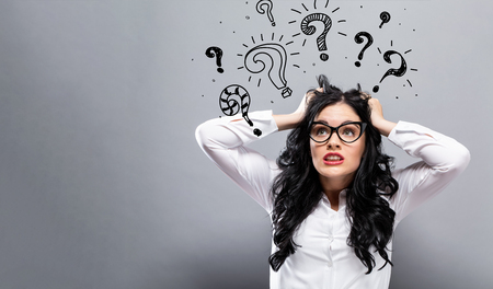 Question marks with young business woman feeling stressed