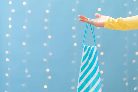 Woman holding a shopping bag on a shiny light blue background