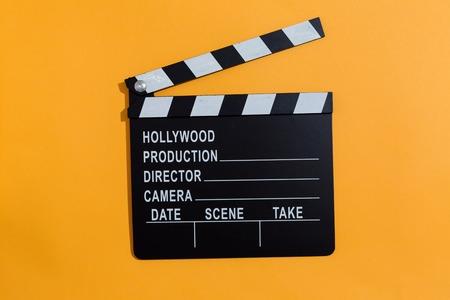 Movie slateboard clapper on a orange background