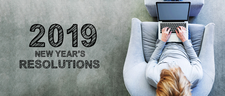 2019 New Years Resolutions with man using a laptop in a modern gray chair