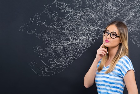 Confused concept with young woman in front of a blackboard