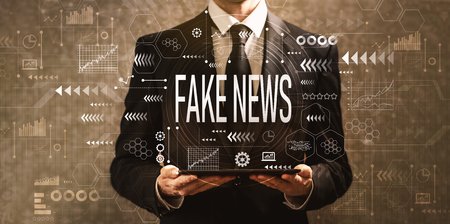 Fake news with businessman holding a tablet computer on a dark vintage background Stock Photo