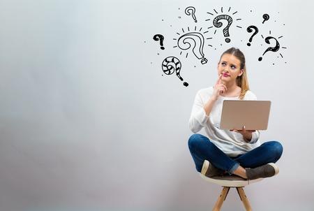 Vraagtekens met jonge vrouw die haar laptop op een grijze achtergrond gebruikt Stockfoto