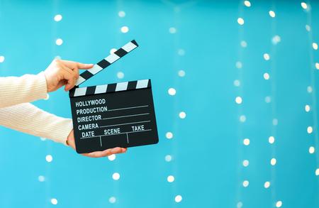 Movie slateboard clapper on a shiny light blue background
