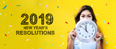 2019 New Years Resolutions with young woman holding a clock showing nearly 12 Фото со стока