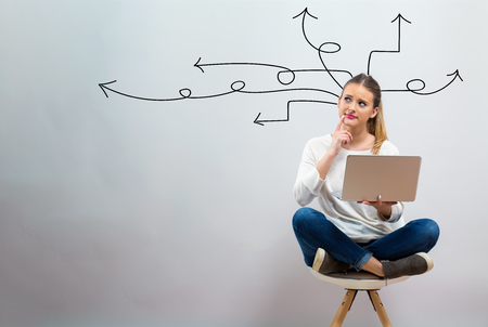 Idea arrows with young woman using her laptop on a grey background