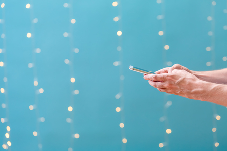 Young man using his smartphone on a shiny light blue background