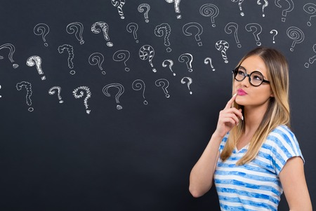 Small question marks with young woman in front of a blackboard