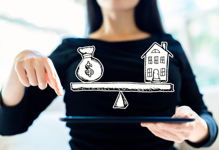 House and money on the scale with woman using her tablet Stock Photo