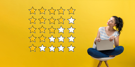 Rating with yellow stars with young woman using a laptop computer