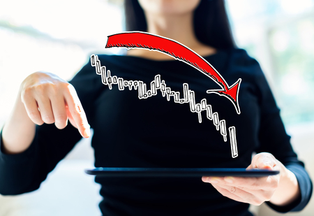 Market down trend chart with woman using her tablet Stock Photo