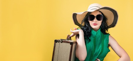 Young woman with a suitcase travel theme on a yellow background Stock Photo