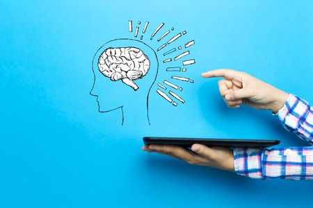 Brain illustration with a tablet computer on a blue background Фото со стока
