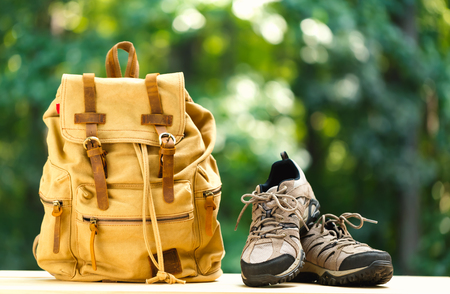 A backpack with hiking boots on a bright summer day in the forest