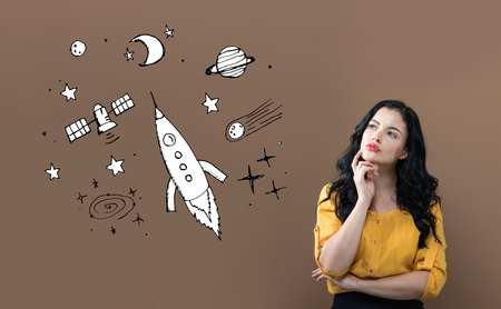 Dream of space and rocket with young businesswoman on a brown background
