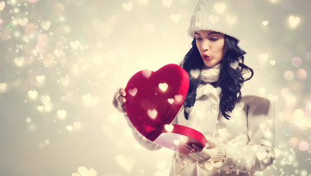 Happy young woman holding a big heart gift box Stock Photo