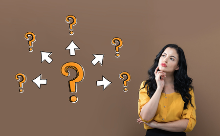 Grandi e piccoli punti interrogativi con frecce con giovane donna d'affari su sfondo marrone