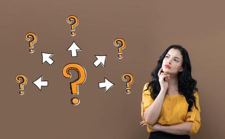 Grote en kleine vraagtekens met pijlen met jonge zakenvrouw op een bruine achtergrond