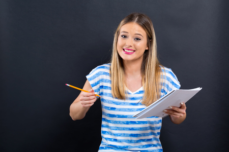 Young woman with notebook and pencil on a black background