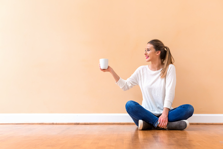 Young woman drinking a cup of coffee against a big interior wall