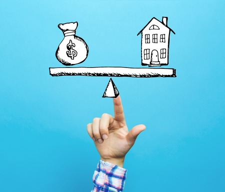 House and money on the scale with hand on a blue background Stok Fotoğraf