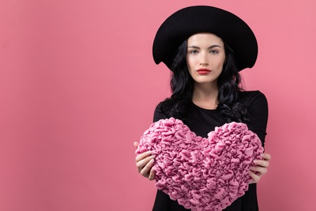 Woman holding a heart cushion in Valentines day theme on a pink background