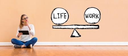 Balance zwischen Leben und Arbeit mit einer jungen Frau, die einen Tablet-Computer hält Standard-Bild