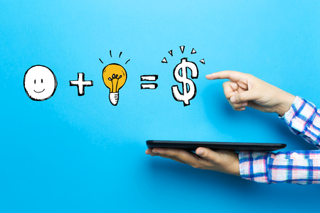 Good idea equals money with a tablet computer on a blue background