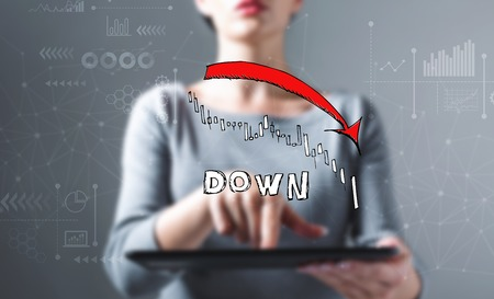 Market down trend chart with business woman using a tablet computer Stok Fotoğraf - 115151274