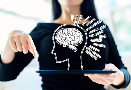 Brain illustration with woman using her tablet Фото со стока