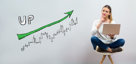 Market up trend chart with young woman using her laptop on a grey background